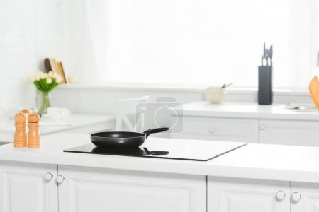 Photo for Modern kitchen with white counter, cooker and frying pan - Royalty Free Image