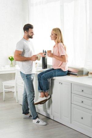 Photo pour Beau couple avec des tasses de café pendant le petit déjeuner à la cuisine - image libre de droit