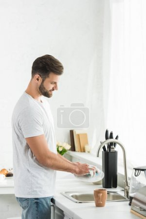 Photo for Handsome man washing dishes at kitchen in morning - Royalty Free Image