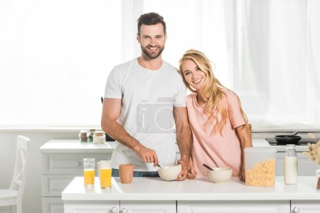 happy couple with bowls of cereal during breakfast at kitchen