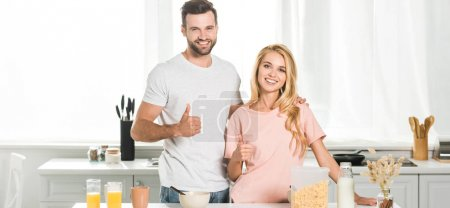 Photo for Panoramic shot of beautiful couple showing thumbs up during breakfast at kitchen - Royalty Free Image