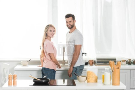 Photo for Beautiful couple looking at camera during breakfast at kitchen - Royalty Free Image
