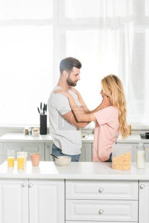Photo pour Couples embrassant pendant le petit déjeuner à la cuisine le matin - image libre de droit