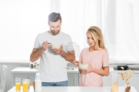 Photo pour Couples heureux mangeant des céréales pendant le petit déjeuner à la cuisine - image libre de droit