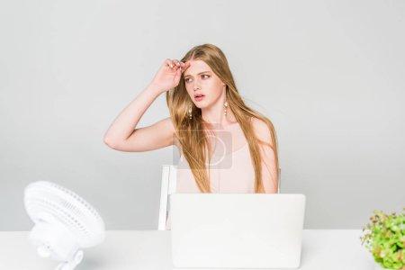 Photo pour Fille souffrant de la chaleur avec le ventilateur électrique au bureau d'ordinateur sur le gris - image libre de droit