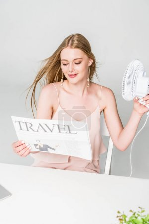 beautiful young woman with Electric Fan and travel newspaper suffering from heat on grey