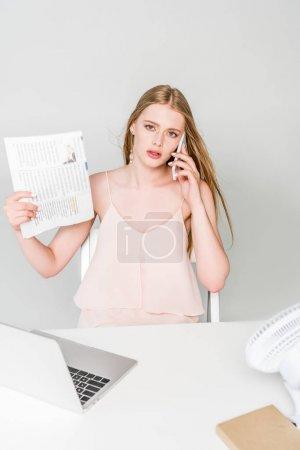 Photo pour Belle fille souffrant de chaleur, en agitant le journal et en parlant sur smartphone sur le gris - image libre de droit