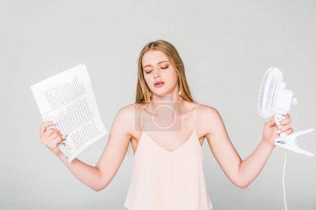 Photo pour Belle jeune femme avec ventilateur électrique et journal souffrant de la chaleur sur le gris - image libre de droit