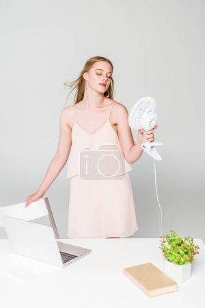 Photo pour Belle fille souffrant de chaleur avec ventilateur électrique près du bureau d'ordinateur sur le gris - image libre de droit