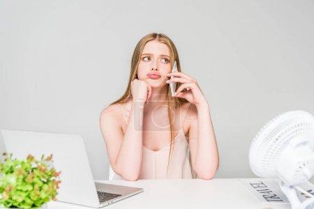 Photo pour Belle fille parlant sur le smartphone et souffrant de la chaleur au bureau d'ordinateur d'isolement sur le gris - image libre de droit