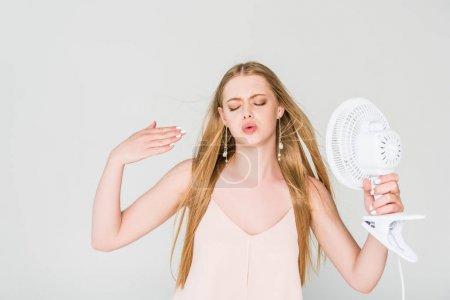Photo pour Belle jeune femme souffrant de chaleur, geste et tenue Ventilateur électrique isolé sur gris - image libre de droit