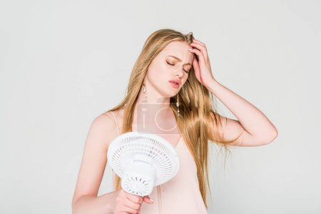 Photo pour Jeune femme souffrant de chaleur et tenant Ventilateur électrique isolé sur gris - image libre de droit