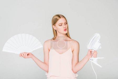 Photo pour Jeune femme retenant le ventilateur électrique et le ventilateur de main et souffrant de la chaleur isolée sur le gris - image libre de droit