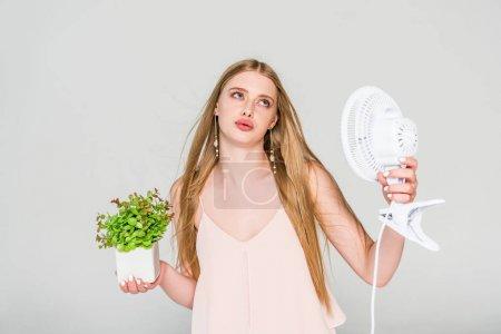 Photo pour Belle jeune femme avec ventilateur électrique et pot de fleur souffrant de la chaleur isolée sur le gris - image libre de droit