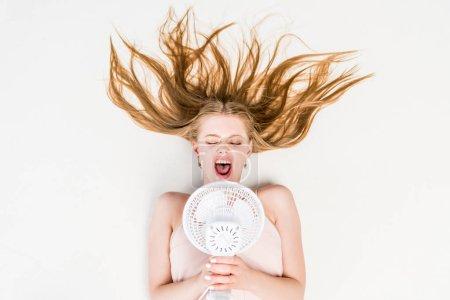 Photo pour Vue de dessus de fille criant dans ventilateur électrique et souffrant de chaleur sur blanc - image libre de droit