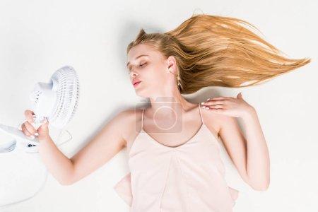 Photo pour Vue de dessus de la fille tenant ventilateur électrique tout en souffrant de chaleur sur blanc - image libre de droit