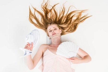 Photo pour Vue de dessus de la belle jeune femme avec ventilateur électrique et ventilateur à main souffrant de chaleur sur blanc - image libre de droit