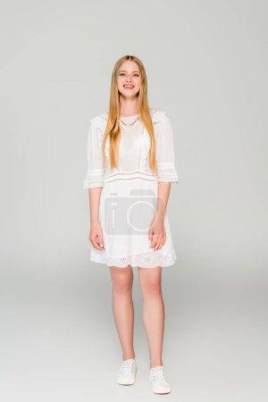 Photo pour Belle fille de sourire dans la robe blanche regardant l'appareil-photo sur le gris - image libre de droit