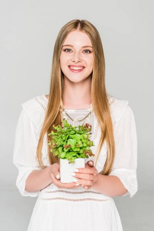 Photo for Beautiful girl holding flowerpot with plant isolated on grey - Royalty Free Image