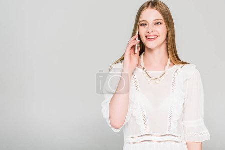 Photo for Beautiful girl talking on smartphone isolated on grey - Royalty Free Image