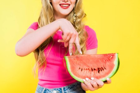 Photo for Cropped view of girl walking with fingers on watermelon On yellow - Royalty Free Image