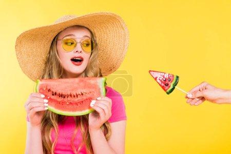 Photo pour Belle fille surprise en paille chapeau avec pastèque regardant sucette isolé sur jaune - image libre de droit