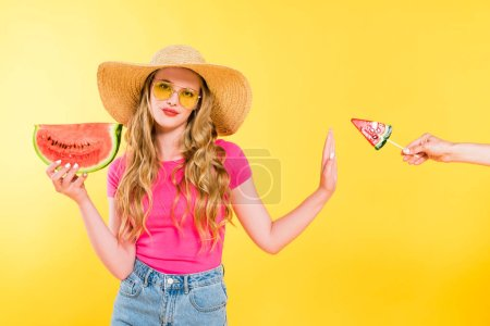 Photo for Dissatisfied girl with watermelon gesturing and refusing lollipop on yellow - Royalty Free Image