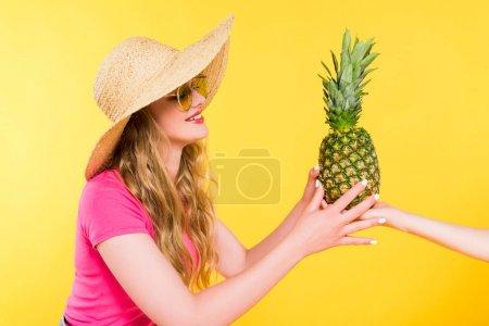 Photo pour Belle fille en paille Chapeau donnant l'ananas à la femme isolé sur jaune - image libre de droit