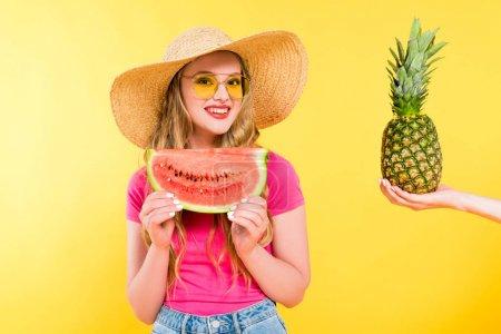 Photo pour Belle fille en paille Chapeau avec pastèque près de femme tenant l'ananas Sur jaune - image libre de droit