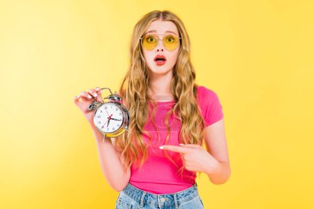 Photo for Beautiful surprised girl in sunglasses pointing with finger at alarm clock On yellow - Royalty Free Image