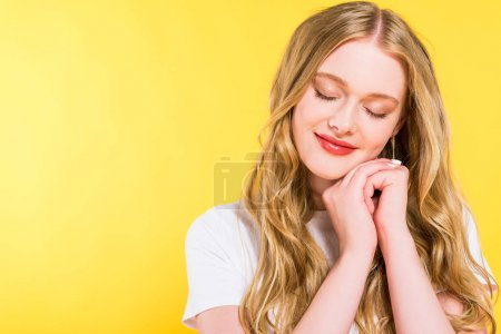 Photo for Beautiful blonde young woman with eyes closed and folded hands Isolated On yellow - Royalty Free Image