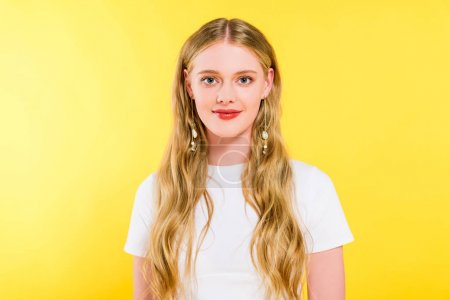 Photo pour Belle jeune femme blonde dans le T-shirt blanc regardant l'appareil-photo d'isolement sur le jaune - image libre de droit