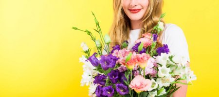 Photo for Panoramic shot of blonde girl with flowers Isolated On yellow - Royalty Free Image