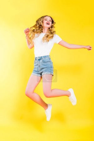 Photo for Beautiful happy blonde young woman jumping On yellow - Royalty Free Image