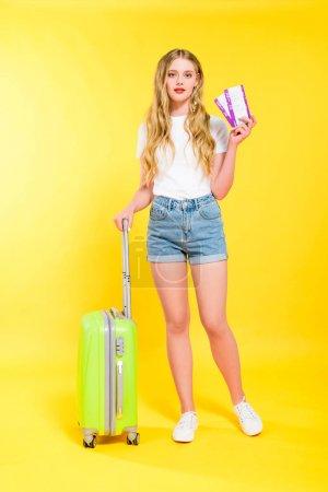 Photo pour Belle fille avec valise et billets d'avion sur jaune - image libre de droit