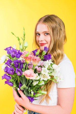 Photo pour Belle fille blonde avec des fleurs regardant l'appareil-photo sur le jaune - image libre de droit