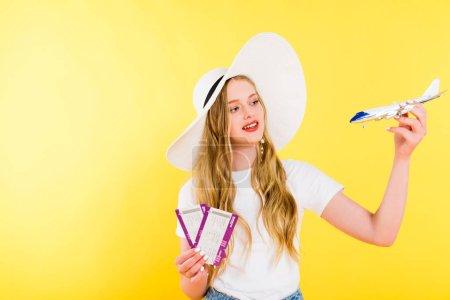 schönes Mädchen mit Flugzeugmodell und Flugtickets auf gelb