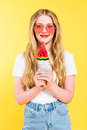 Photo for Beautiful girl with lollipop in shape of watermelon looking at camera On yellow - Royalty Free Image