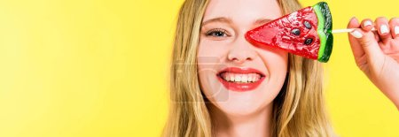 Foto de Panoramic shot of beautiful smiling girl with lollipop in shape of watermelon Isolated On yellow - Imagen libre de derechos