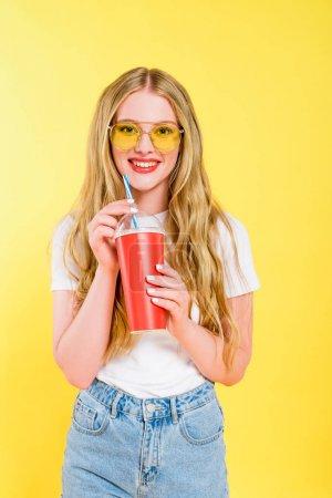 Photo pour Belle fille souriante dans des lunettes de soleil avec boisson dans une tasse jetable isolé sur jaune - image libre de droit