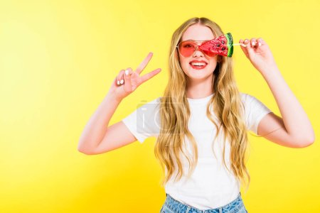 Photo for Beautiful happy girl in sunglasses with lollipop in shape of watermelon doing Peace Sign On yellow - Royalty Free Image