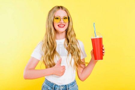 Photo pour Belle fille dans des lunettes de soleil avec la boisson dans la tasse jetable faisant le pouce vers le haut sur le jaune - image libre de droit