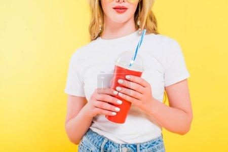 Photo pour Vue recadrée de boisson de fixation de fille dans la tasse jetable d'isolement sur le jaune - image libre de droit