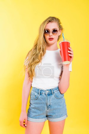 Photo for Beautiful girl in sunglasses with drink in disposable cup On yellow - Royalty Free Image