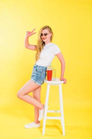 Photo pour Belle fille dans des lunettes de soleil près de la présidence avec la boisson de soude affichant le signe de paix sur le jaune - image libre de droit