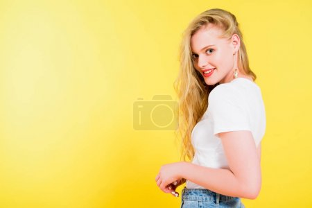 Photo for Beautiful smiling blonde young woman looking at camera On yellow - Royalty Free Image