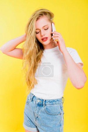 Foto de Hermosa chica hablando en el teléfono inteligente aislado en amarillo - Imagen libre de derechos