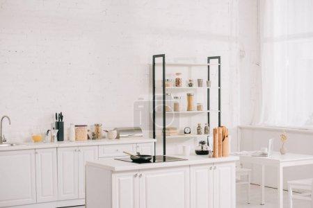 Photo pour Cuisine spacieuse avec mobilier moderne blanc et rack avec bocaux - image libre de droit