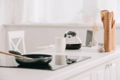 kitchen table with frying pan on cooking surface near coffee pot and cup