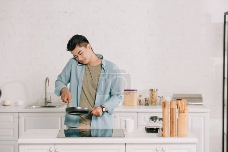 Photo for Handsome asian man preparing breakfast on frying pan while talking on smartphone in spacious kitchen - Royalty Free Image